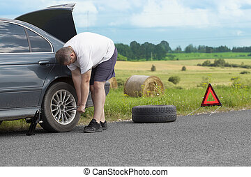 Man changing tire on the road
