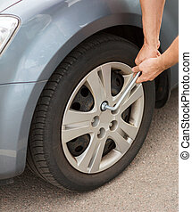 man changing tire - transportation and vehicle concept - man...
