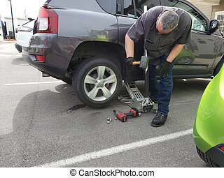 Man changing tire to spare in parking lot.