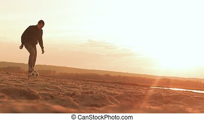 man chasing a ball slow motion video evening at sunset -...