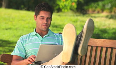 Man chatting on a laptop outdoors - Man relaxing and ...