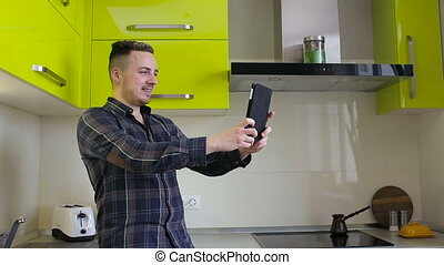 Man chatting on tablet computer in kitchen