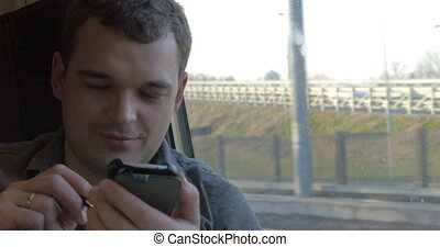 Man chatting on the mobile during train ride - Young smiling...