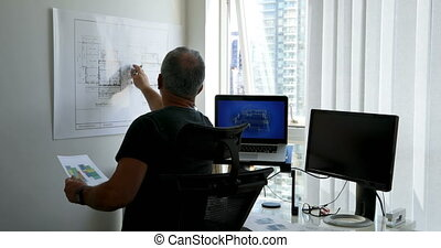 Man checking blueprint on desk 4k - Man checking blueprint...