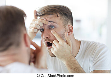 Portrait of handsome young man checking eyes looking at his reflection in mirror, copy space