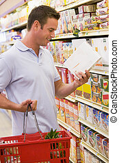 Man checking food labelling in supermarket - Man checking ...