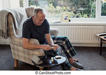Man Checking Glucose Levels at Home - Senior diabetic man is...