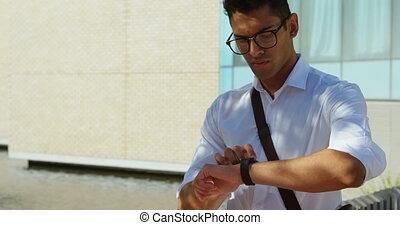 Man checking his smartwatch on street 4k - Man checking his...
