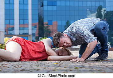 Man checking if woman's breathing on the street