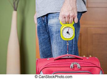 Man checking luggage weight with steelyard balance - Man...