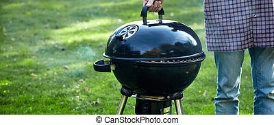 Man checking on the fire in a portable BBQ