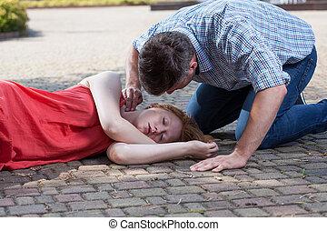 Man checking pulse of fainted girl - Adult man checking...