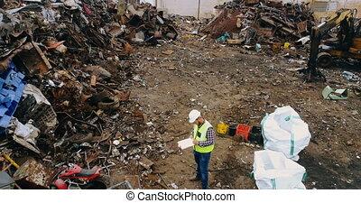Drone shot of man checking scrap in scrapyard 4k