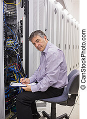 Man checking servers and writing on clipboard