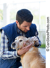 man checking the dogs ear