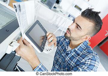 man checking the screen of a printer