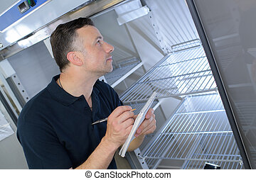 man checking the state of a refrigerator