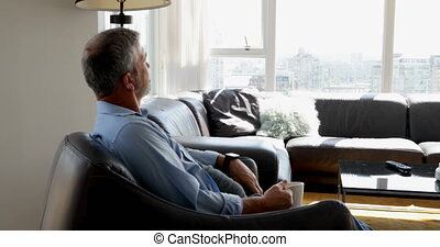 Man checking time on smartwatch while having coffee 4k - Man...