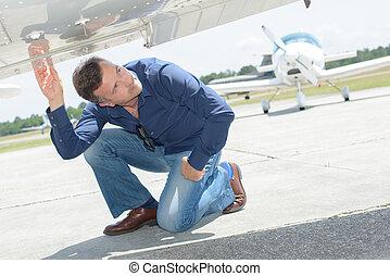 Man checking underside of aircraft