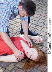 Man checking up consciousness of young girl