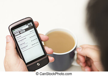 A man checks his bank using mobile banking over a coffee