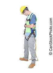A construction worker double checks fastenings on a safety climbing harness dressed in other safety gear and isolated on white.