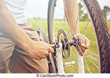 Man checks wheel of bicycle