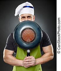 Man chef hiding his face behind a wok pan