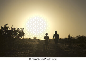 Man and child walking the dog at sunset in the form of the flower of life