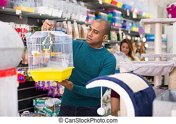 Man chooses bird cage at pet store