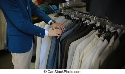 Man choosing a suit at clothing store