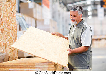 Man choosing and buying construction wood in a DIY store for...