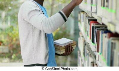 man choosing book in library