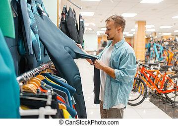 Man choosing cycling suit, shopping in sports shop