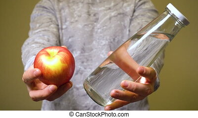 Man choosing fresh organic apple and clean eco water. ...