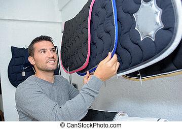 Man choosing horse's blanket in store