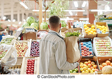Man choosing juicy fruits
