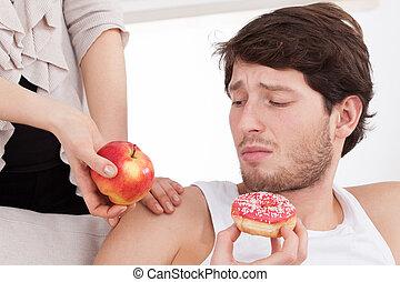Man choosing junk food instead of healthy food