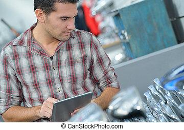 man choosing metallic tap in household store
