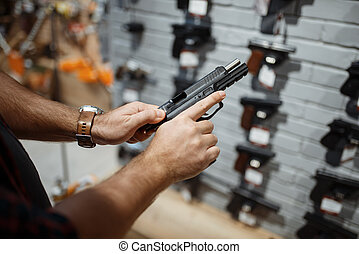 Man choosing new handgun in gun shop - Man choosing new ...