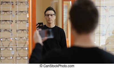 Man choosing new pair of glasses at optometrist, wide...
