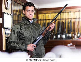 Man choosing rifle in shop