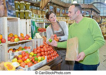 Man choosing tomatoes in store