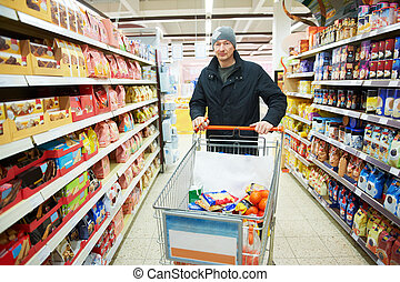 Adult man choosing produces in vegetable department of mall supermarket during shopping
