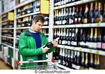 Man choosing wine in supermarket