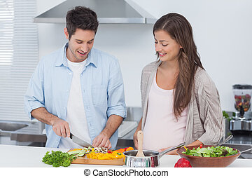 Man chopping mushrooms next to his pregnant partner