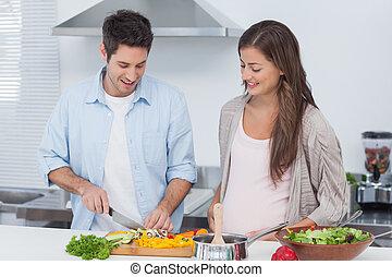 Man chopping mushrooms next to his pregnant partner