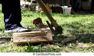 Man Chopping Wood Outdoors With Axe