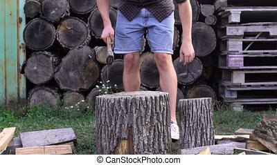 Man chopping wood with axe, slow motion shoot