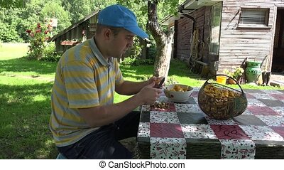 man clean chanterelle mushrooms at table in country yard. 4K
